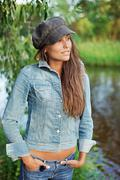 Attractive young woman dressed in jean jacket and beret Stock Photos