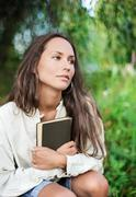 thoughtful young lady with book - stock photo