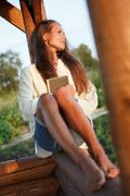 Young lady with book in summerhouse on sunset Stock Photos