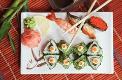 Bamboo rolls and sushi with a shrimp, eel and caviar of flying fish Stock Photos