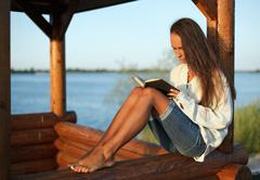 young woman reading book in summerhouse on sunset - stock photo