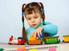 little girl preschooler playing with toy railway - stock photo