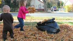 Small Children helping to clean up fall leaves Stock Footage