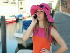 Rich woman in hat talking on cellphone in Venice Stock Footage