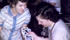 Women LOOKING PHOTO ALBUM Family Photos 1950s Vintage 8mm Film Home Movie 5067 Stock Footage