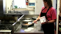 Woman spreading whip cream on cake in professional kitchen Stock Footage