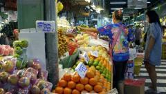 Woman weighing bag of grapes at a Bangkok fresh fruit market Stock Footage