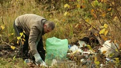 Man collects waste in bag near forest Stock Footage