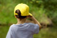 little boy with yellow cap saluting  nature - stock photo