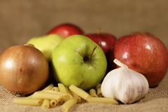 Apples, onions, garlic and pasta  Stock Photos