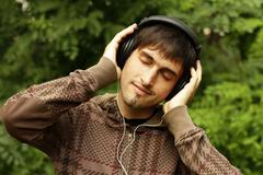 Guy with headphones is listening to music - stock photo