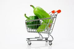 Green sweet pepper paprika  in shopping trolley on white background Stock Photos