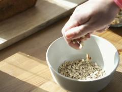 Stock Video Footage of Hand adding walnuts and raisins to muesli in bowl NTSC