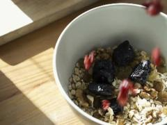 Hand adding prune and cranberries to muesli in bowl NTSC - stock footage