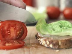 Female hand slicing and putting tomato on slice of bread NTSC Stock Footage