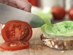 Female hand slicing tomato, slow motion shot at 240fps NTSC Stock Footage