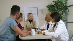 Doctors in a meeting smile at camera Stock Footage