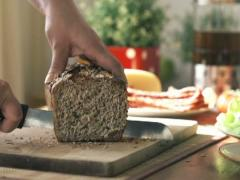 Stock Video Footage of Slicing whole grain bread, slow motion shot at 240fps NTSC