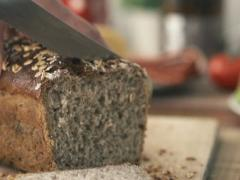Male hand licing whole grain bread NTSC Stock Footage