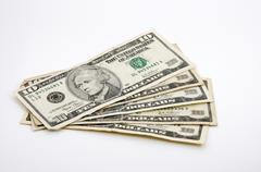 Ten-dollar bills spread out on white Stock Photos