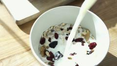 Pouring milk into bowl with muesli HD Stock Footage