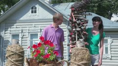 Couple play near stylized fence of village house Stock Footage
