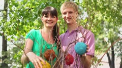 Couple hold decorative balls on bush and smile Stock Footage