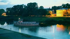 Ship turns on river near coastal houses at night Stock Footage