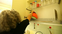 Senior Woman Puts Dishes on Drier Stock Footage