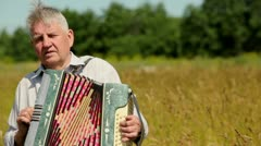 Grandfather in shirt plays on accordion in field - stock footage