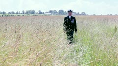 Old man in marine uniform approach among grass in field Stock Footage