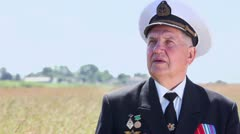 Old man in marine uniform stands in field Stock Footage