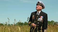 Old man in marine uniform stands in field near forest Stock Footage