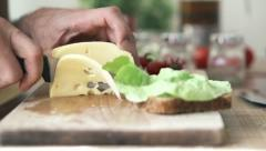 Hand cutting yellow cheese with knife, slow motion shot at 240fps HD Stock Footage