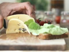 Hand cutting yellow cheese with knife, slow motion shot at 240fps NTSC Stock Footage