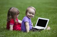 Little boy and girl using a little Laptop while sitting on meadow. Stock Photos