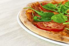 Pizza margharita with arugula and slices of tomato - stock photo