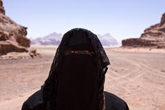 Portrait of Bedouin woman with Burka in desert - stock photo