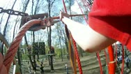 Boy goes on red rope ladder in adventure park Stock Footage