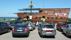 Parking with cars before cafe Botik in form of wooden ship Stock Footage