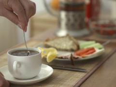 Hand adding sugar to tea and mixing it with spoon NTSC Stock Footage