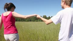 Man and woman go forward across field holding hands Stock Footage