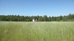Man and woman go back across field at summer Stock Footage