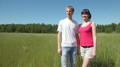 Guy with girl stand nearby in field, look and specify afar Stock Footage