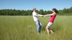 Guy with girl are turned holding hands in field near wood Stock Footage