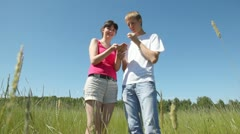 Girl and guy stand in field and eat wild strawberry Stock Footage