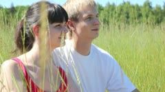 In high grass sit next guy to girl and look afar Stock Footage