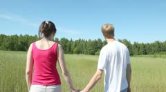 Man and woman go across field to wood holding hands Stock Footage