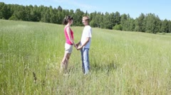 Man and woman stand in field with grass and to hold hands Stock Footage