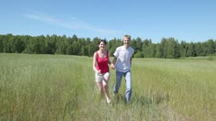Man and woman holding hands also run forward across field Stock Footage